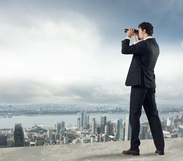 Biznesmen patrzy na miasto z dachu przez lornetkę