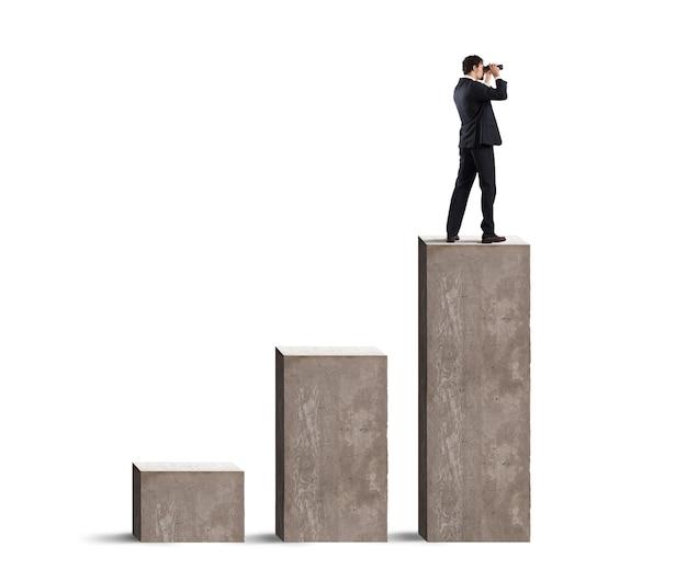 Biznesmen patrzy na przyszłość gospodarczą przez lornetkę nad statystyką