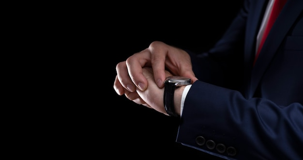 Biznesmen patrzy na zegarek na czarnym tle z miejscem na tekst.