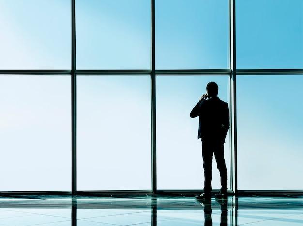 Biznesmen patrzy przez panoramiczne okno.