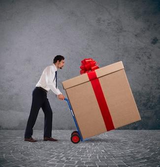 Biznesmen pcha ciężki wielki prezent z wózkiem