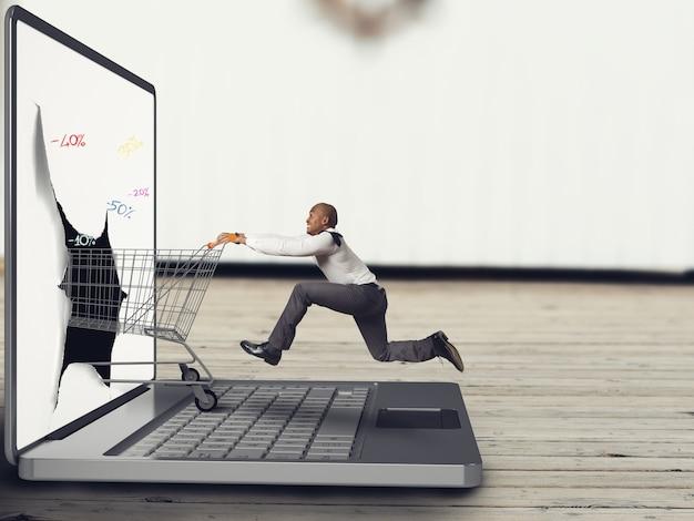 Biznesmen pcha koszyk na klawiaturze laptopa