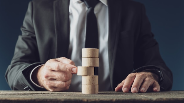 Biznesmen pchanie drewniane koło cięcia w stos z nich w koncepcyjny obraz wizji biznesowej i strategii.