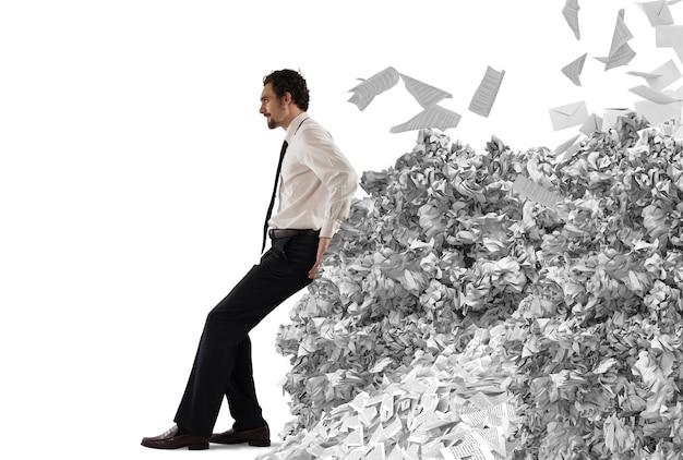 Biznesmen pchanie ze zmęczeniem wielki stos papierkowej roboty