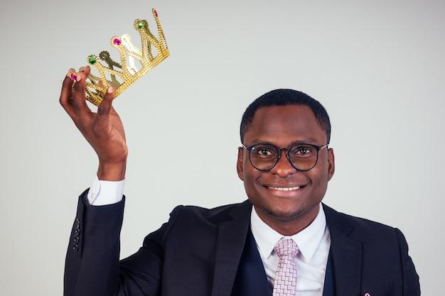 Biznesmen pewnie król w czarnym garniturze klasycznym z krawatem i okularami na głowie na białym tle w studio.