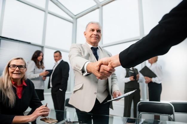 Biznesmen pewnie, ściskając ręce ze swoim partnerem biznesowym. pojęcie współpracy