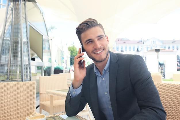Biznesmen picia filiżanki kawy siedząc z telefonem w kawiarni.
