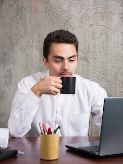 Biznesmen picia herbaty przy biurku.
