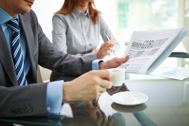 Biznesmen picia kawy i czytanie gazety