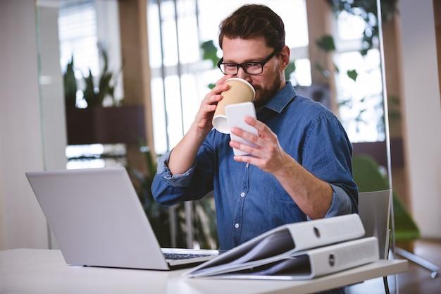 Biznesmen pije biuro podczas gdy używać telefon komórkowego przy kreatywnie biurem