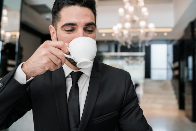 Biznesmen pije kawę przy hotelu lobby.