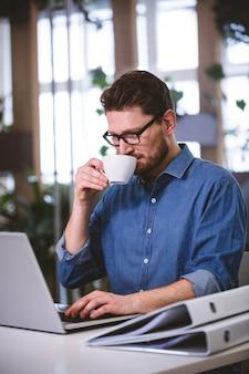 Biznesmen pije kawę przy kreatywnie biurem