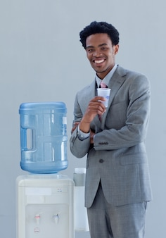 Biznesmen pije od wodnego cooler w biurze