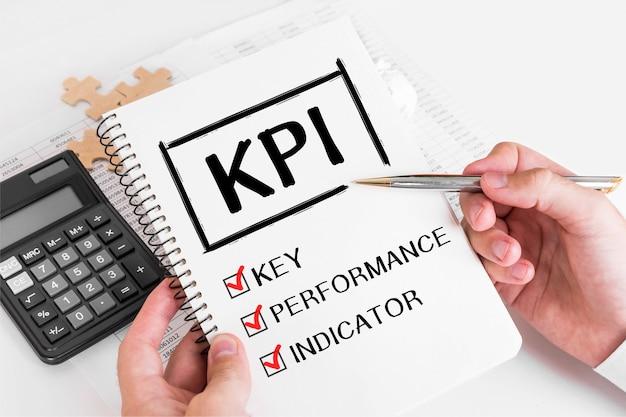 Biznesmen pisania koncepcji kpi w notatce.
