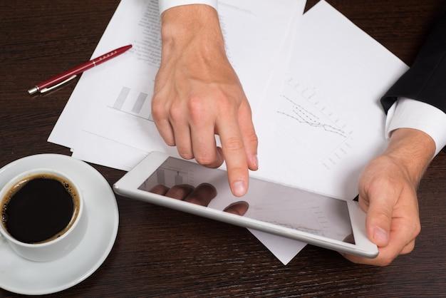 Biznesmen pisania na papierze obok tabletu, kawy, telefonu komórkowego