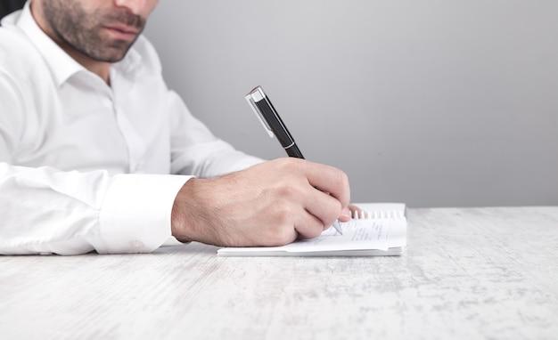 Biznesmen pisania na papierze w biurze.