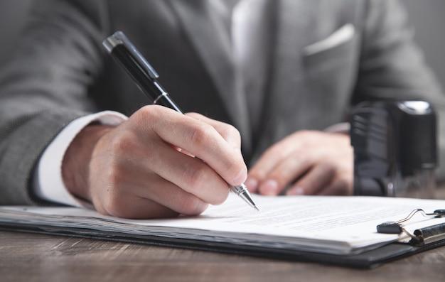 Biznesmen pisania w dokumencie. pieczęć na biurku