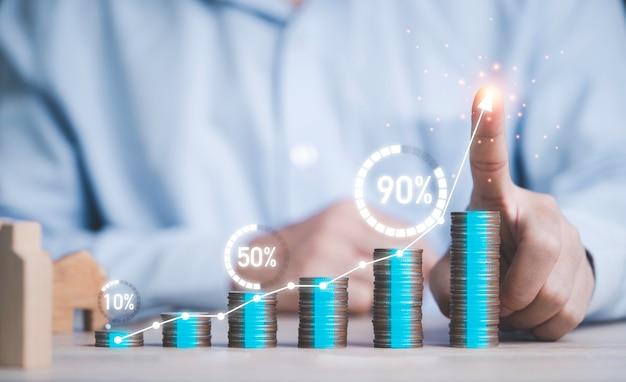Biznesmen pisania wykresu na stosie monet wzrostu z ładowaniem procentowym wirtualnego koła