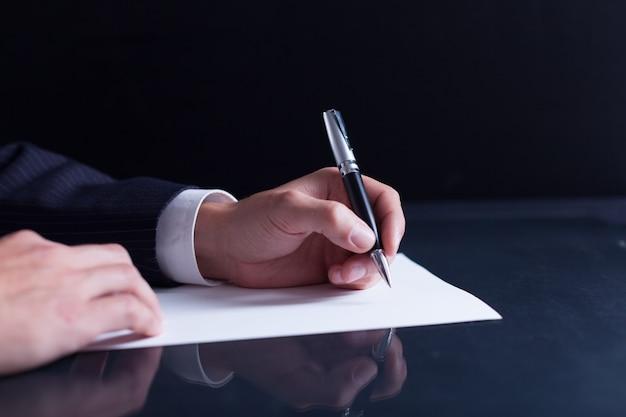 Biznesmen piszący list, notatki lub korespondencję lub podpisujący dokument lub umowę,