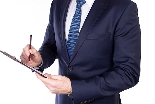 Biznesmen pisze coś ołówkiem w notatniku