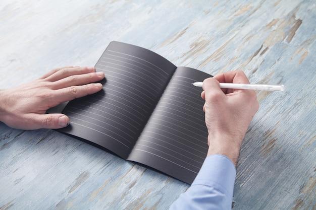 Biznesmen pisze na notatniku w biznesowym biurku.