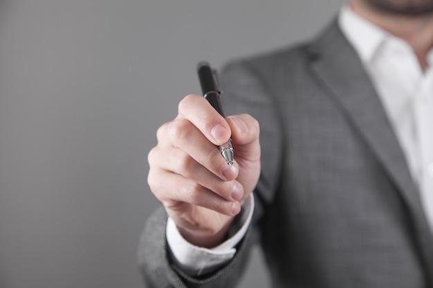 Biznesmen pisze piórem na pustym ekranie.