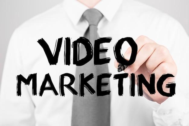 Biznesmen pisze słowo marketing wideo z markerem, koncepcja biznesowa