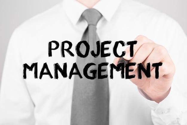 Biznesmen pisze słowo project management z markerem, koncepcja biznesowa