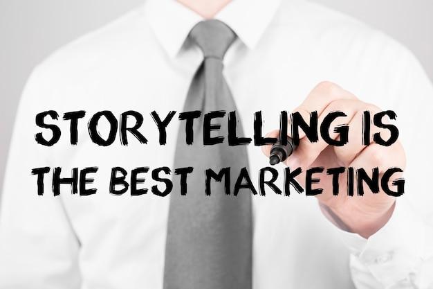 Biznesmen pisze słowo storytelling to najlepszy marketing z markerem, koncepcja biznesowa