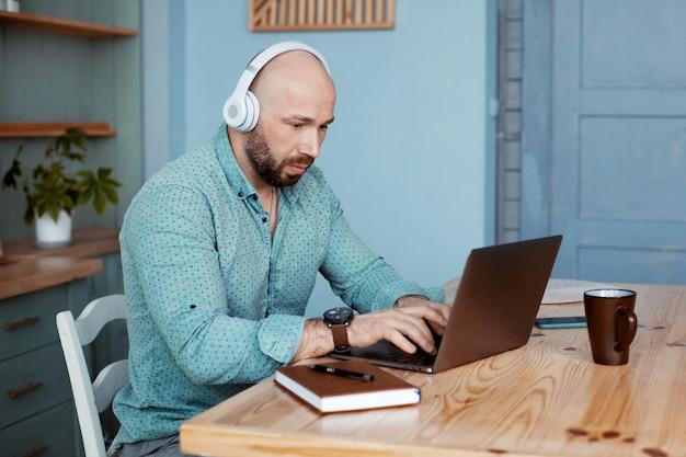 Biznesmen pisze tekst na laptopie i słucha muzyki, pracuje w domu