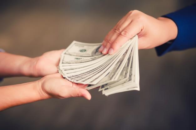 Biznesmen płaci pieniądze - rachunki w dolarach amerykańskich (usd)