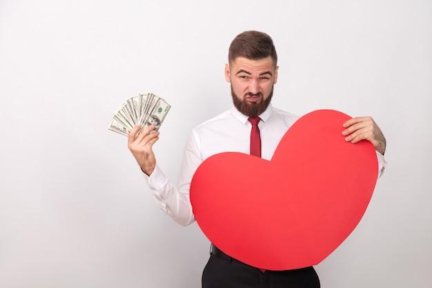 Biznesmen płaci za wielką miłość, trzymając wiele dolarów. wewnątrz, studio strzał, na białym tle na szarym tle