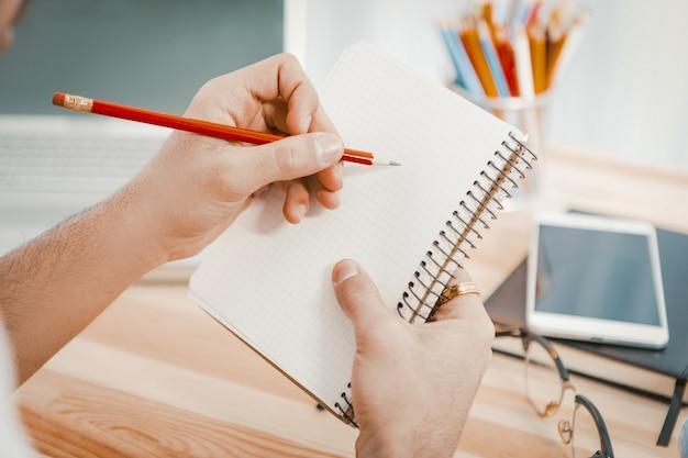 Biznesmen planuje nowy zapis startowy w notatniku.