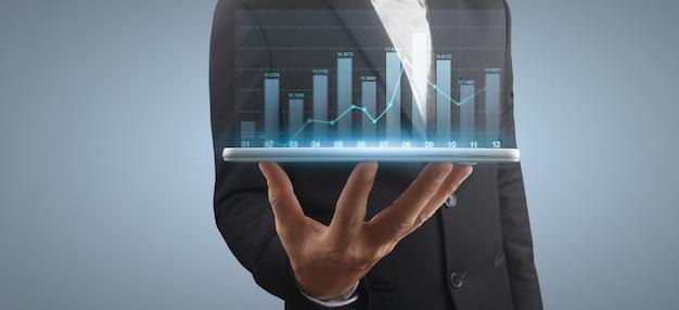 Biznesmen planuje wzrost wykresu i wzrost pozytywnych wskaźników wykresu w swojej firmie, tablet w ręku
