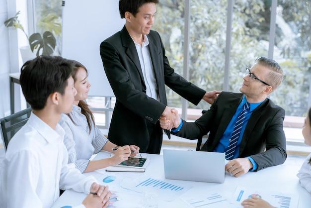Biznesmen podają sobie ręce, zgadzają się na sprzedaż dużych partii, które kończą cel planów marketingowych firmy