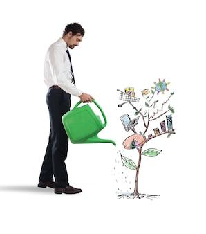 Biznesmen podlewa rośliny wykresem i statystykami