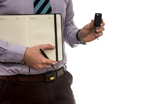 Biznesmen podpisuje umowę kupna lub leasingu lub notatnik napełniania na białym tle
