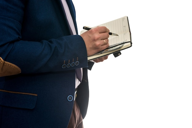 Biznesmen podpisuje umowę kupna lub leasingu lub wypełniania notatnika na białym tle białej ściany