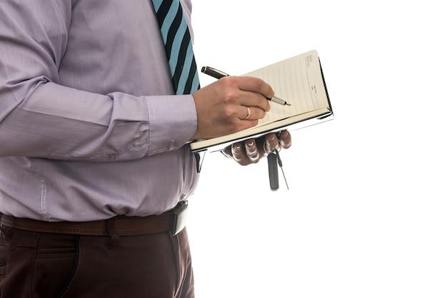 Biznesmen podpisuje umowę kupna lub leasingu lub wypełnianie notatnika na białym tle