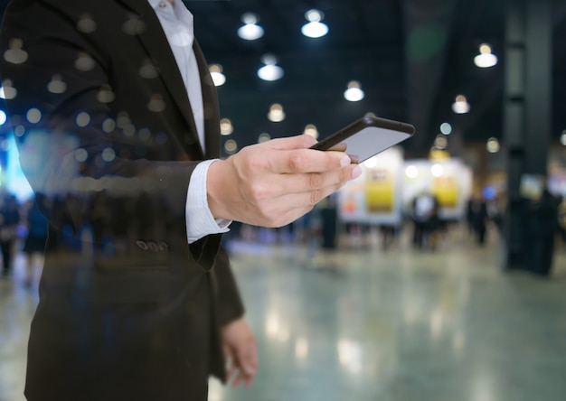 Biznesmen podwójnej ekspozycji w garniturze trzymać smartfona