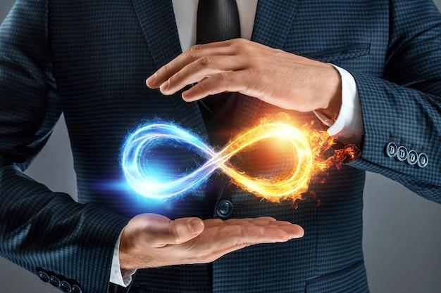 Biznesmen pokazując symbol nieskończoności, symbol lodu ognia