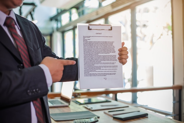 Biznesmen pokazuje kontrakt biznesowy