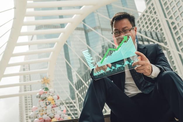 Biznesmen pokazuje rosnące zapasy wirtualnego hologramu.