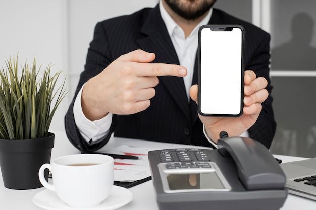 Biznesmen pokazuje telefon komórkowy