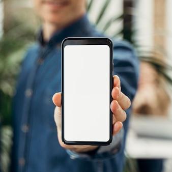 Biznesmen pokazuje telefon z pustym ekranem