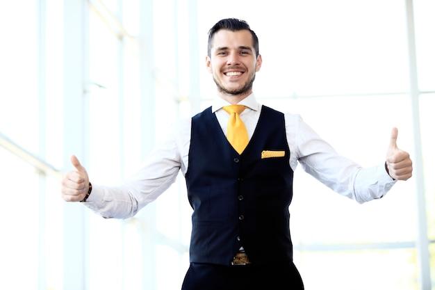 Biznesmen pokazuje znak ok z kciukiem do góry.