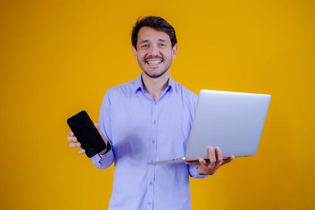 Biznesmen połączony z telefonem komórkowym i notebookiem w rękach