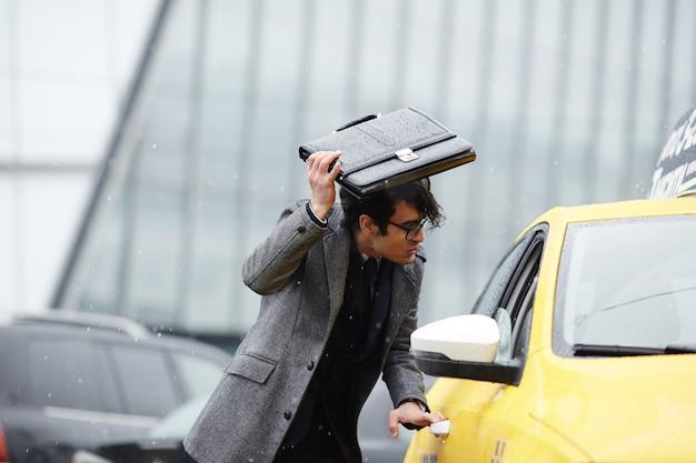 Biznesmen połowu taksówki w burzy