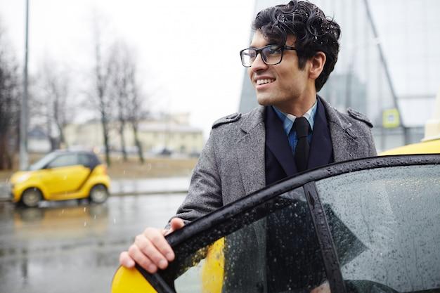 Biznesmen połowu taksówki w mieście