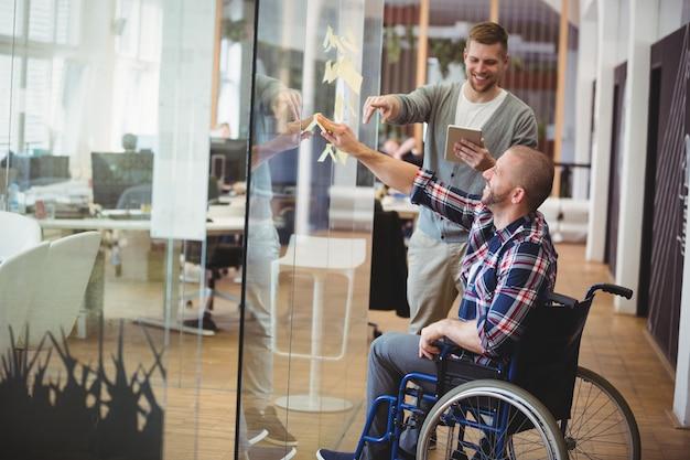 Biznesmen pomaga foru kolegi w kreatywnie biurze